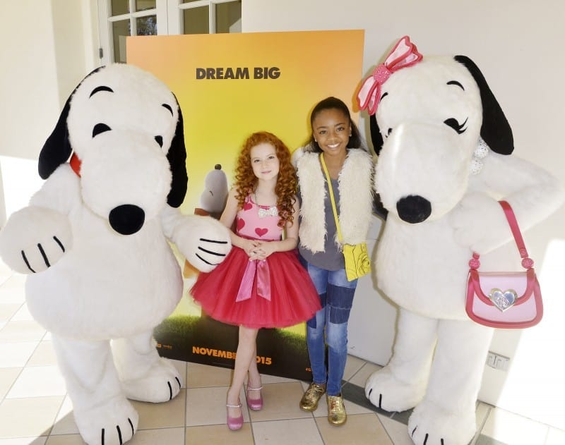"""Doggone Adorable:  Snoopy and his fashionista sister Belle joined Francesca and Skai Jackson from Disney's """"Jessie"""" for a shot in front of the new Peanuts Movie poster displayed at the party."""