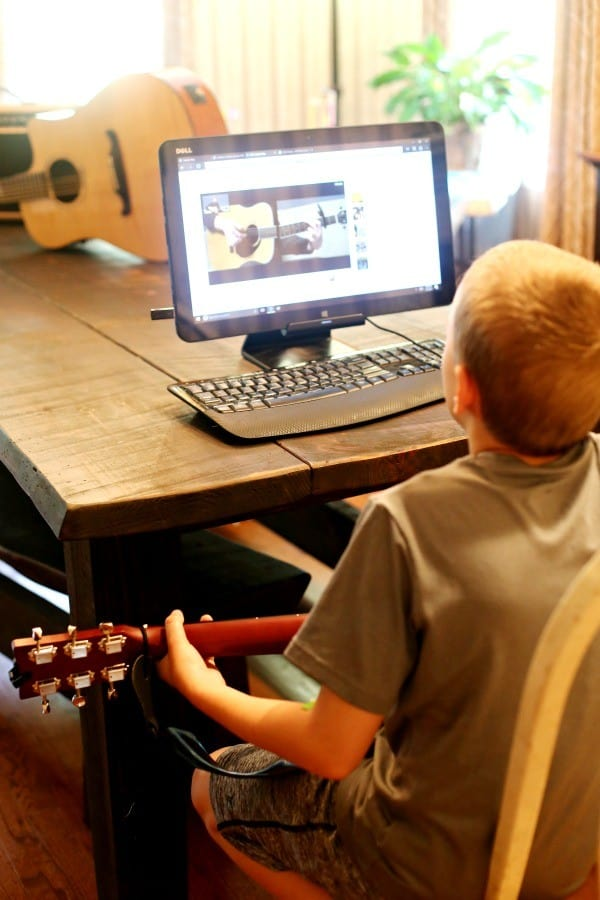 kid learning guitar at home