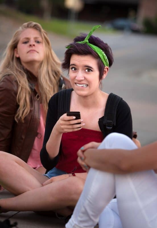 Embarrassed teenage girl holding phone outside with friends