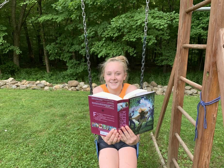 best summer reading books for kids girl reading on swing