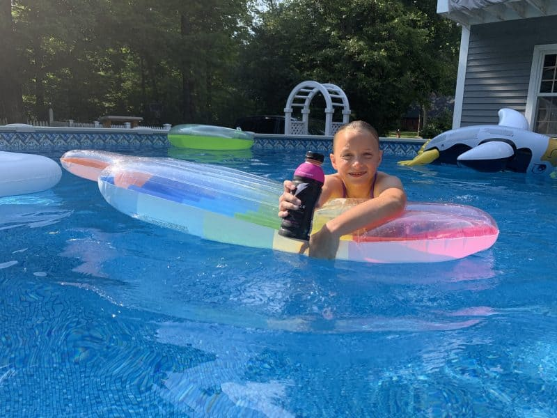 What to Look for in a Sports Drink for Kids girl swimming in pool holding Gatorade Bolt 24