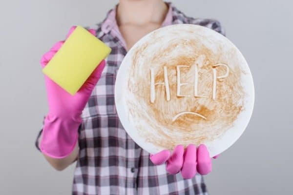 woman holding sponge with dirty plate that says help