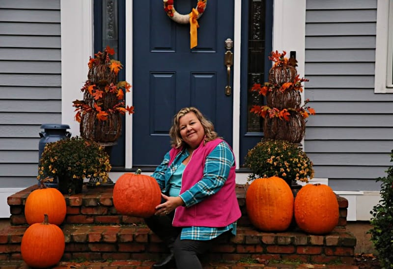 woman in pink fleece vest, flannel tunic and dark denim holding pumpkin sitting on stairs
