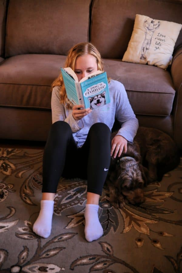 teen reading with dog