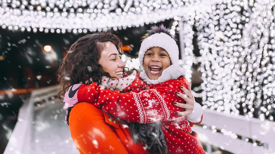 Little black girl enjoying in ice skating with her mother.
