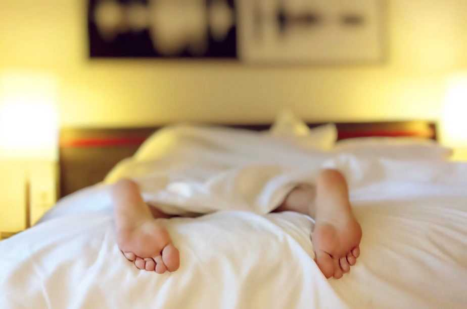 person lying on bed feet sticking out