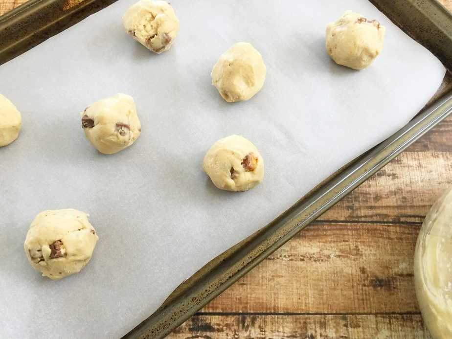 Snickers Cookies spooned onto parchment covered baking sheet before baking