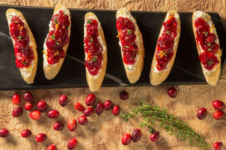 cranberry crostini on black slate with cranberries strewn around