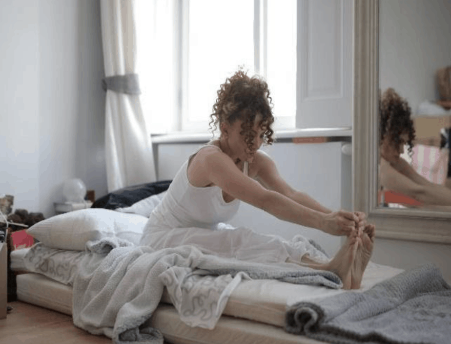 woman stretching on mattress on floor