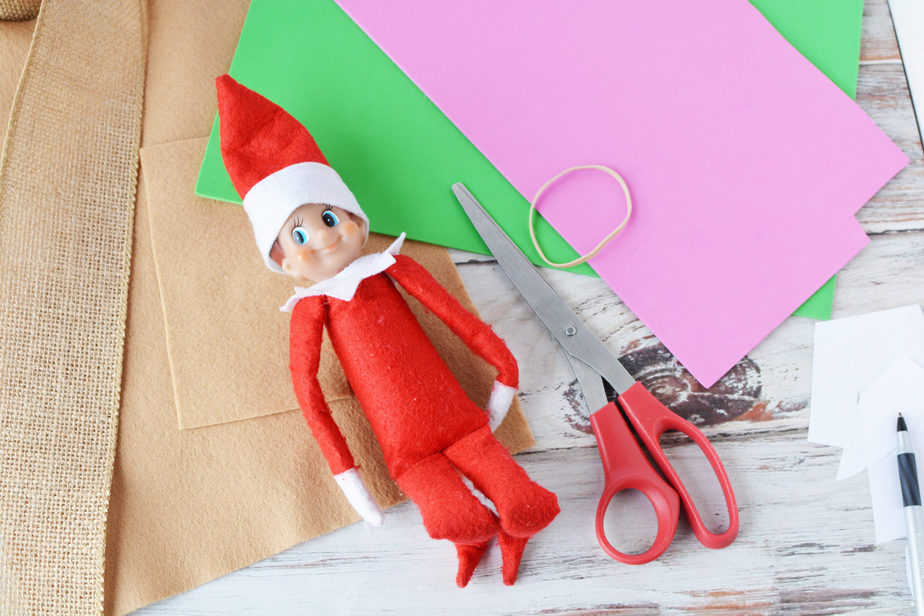 elf on the shelf doll laying on top of felt and foam sheets with scissors