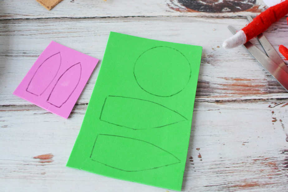 pink and green foam sheets with baby yoda face and ears traced onto them