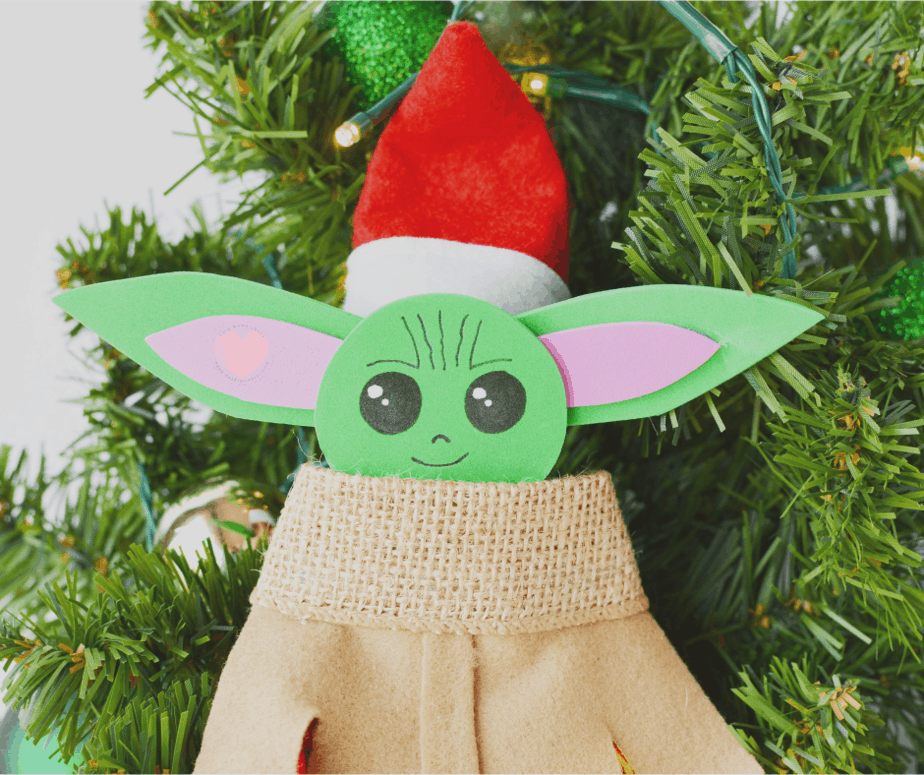 elf on the shelf with baby yoda costume and santa hat on a tree