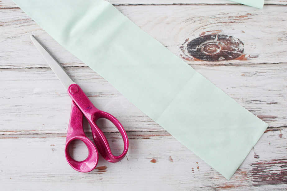 pink sewing scissors and light green fabric swatch