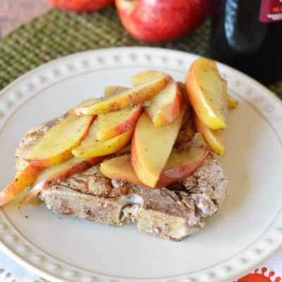 cooked pork chop topped with apples on white plate