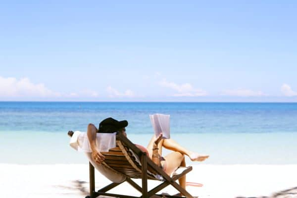 woman with beach hat sitting in chair reading on beach