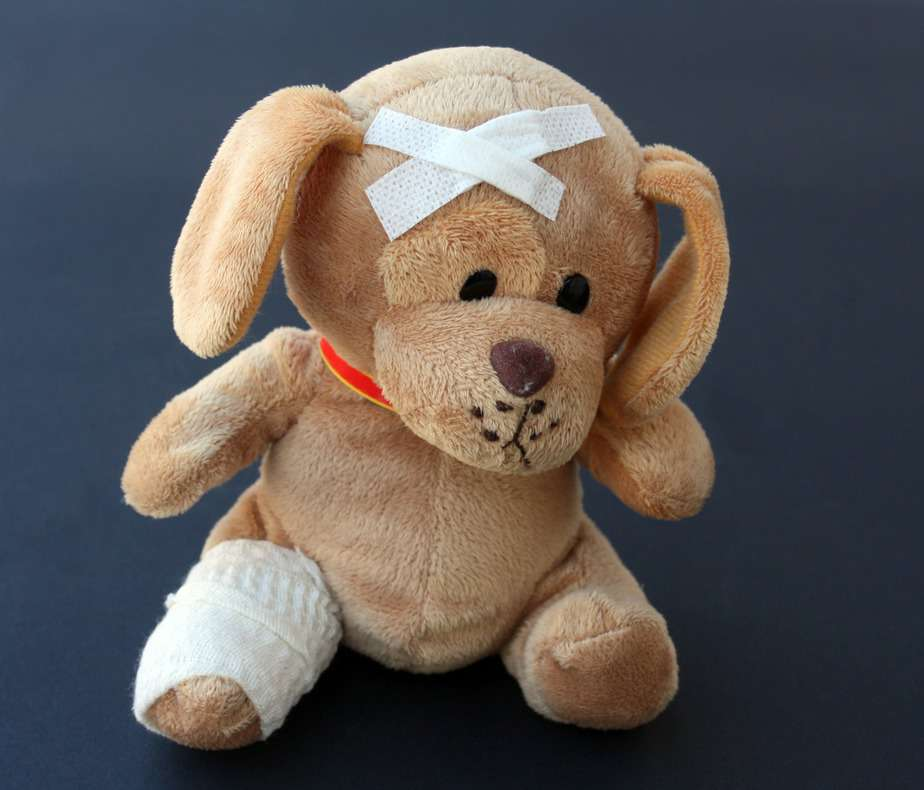 stuffed bear with bandages on head and leg