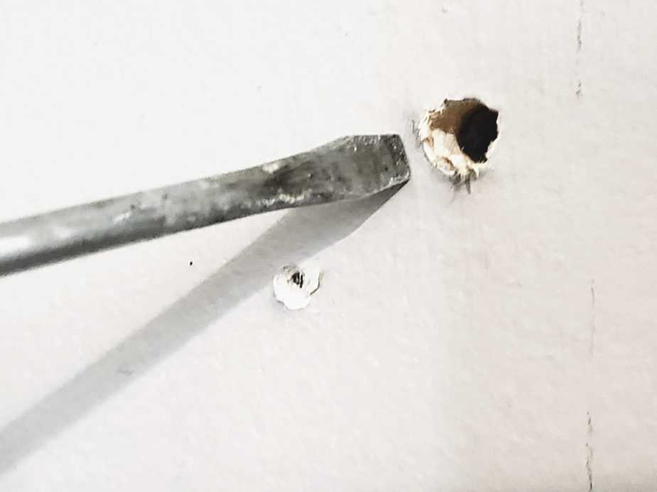 hole in drywall with screwdriver on side