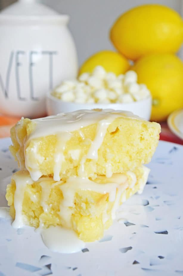 Lemon Blndies Brownies with lemon glaze stacked on white plate with confetti print