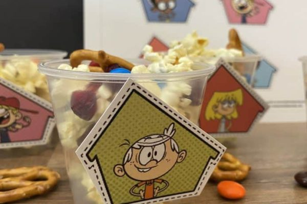 Snack mix in clear plastic cup with cutout image of Lincoln Loud from Nickelodeons the loud house taped to front