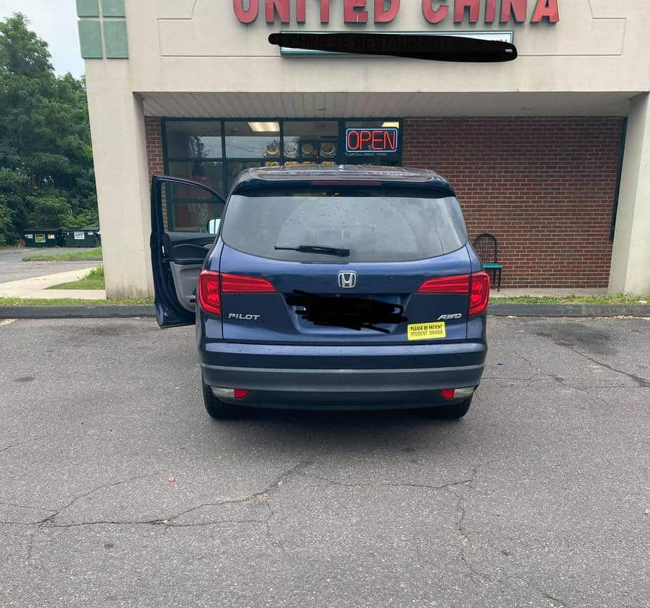 honda pilot family car with student driver magnet on back