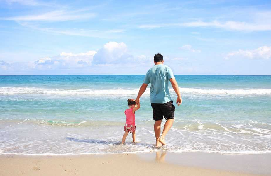 Ensure Your Next Trip Is One Everyone Can Enjoy dad and daughter holding hands walking into ocean